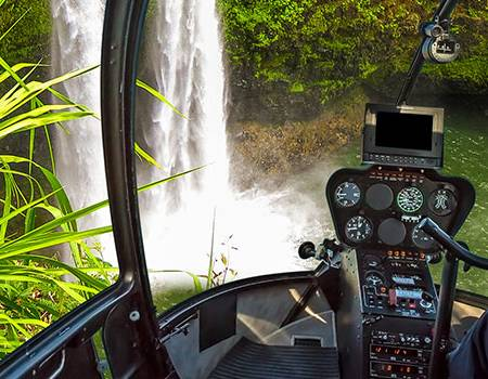 Looking at a Waterfall From a Helicopter In Kauai | Oceanfront Rentals on Kauai